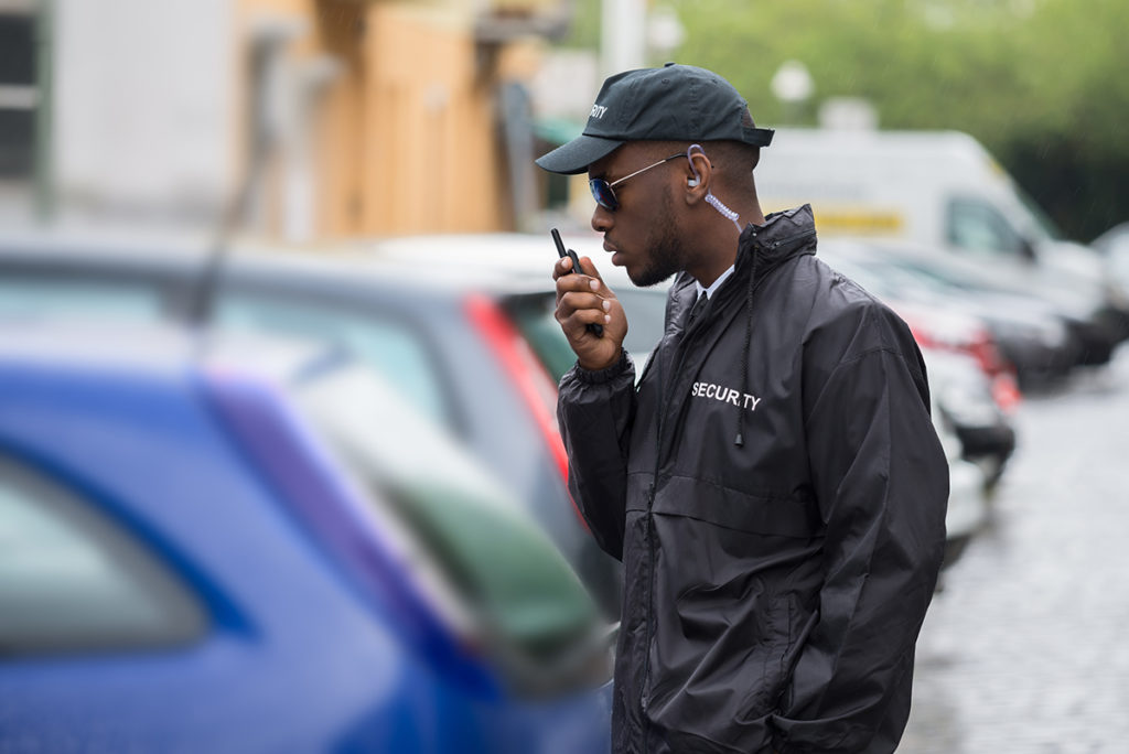 Security guard equipment. A male security guard speaks on a walkie talkie while in a parking lot.