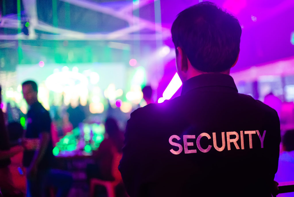 A security guard watches over a crowd in a busy nightclub.