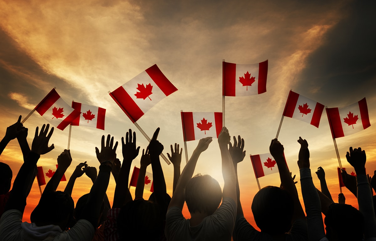 A group of people wave Canadian flags above their head.