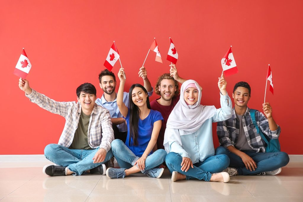 A group of students proudly wave the Canadian flag while sitting together.