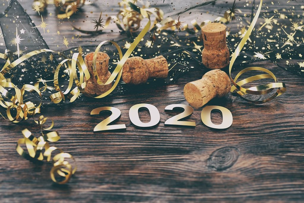 "New Years photo with ""2020"" stickers, champagne corks and confetti."